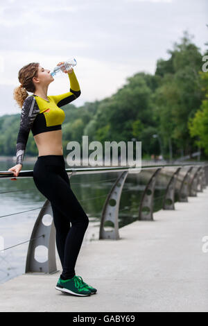 Sportswoman drinking water after running - Stock Photo