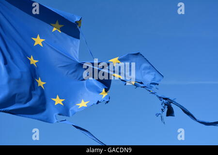 The european union twelve star flag torn and with knots in the wind on blue sky - Stock Photo