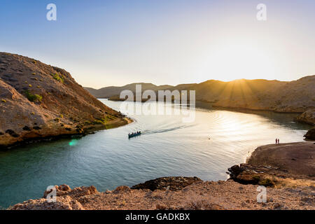 Sunrise in a Fjord in Bandar Khayran with a fishing boat and some tourists looking at the ocean, Sultanate of Oman - Stock Photo