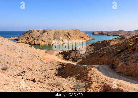 Track going down to a small beach in Bandar Khayran, Sultanate of Oman - Stock Photo