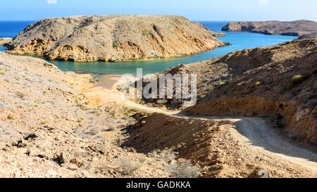 Mountain track going down to a small beach in Bandar Khayran, Sultanate of Oman - Stock Photo