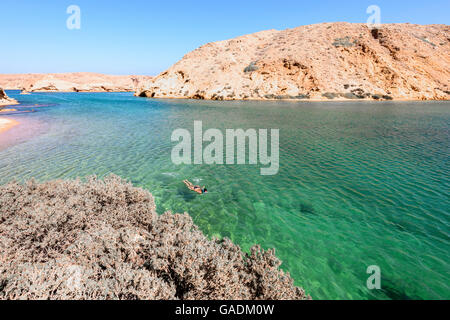 Woman swimming alone in the ocean of a fjord-like of Bandar Khayran,  Sultanate of Oman. A hidden and magnificent - Stock Photo