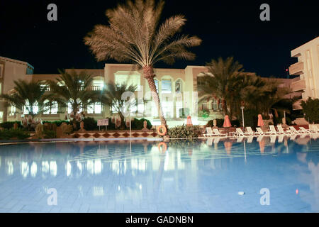 TOZEUR, TUNISIA - SEPTEMBER 16, 2012 : A night shot of the El Mouradi Hotel with the swimming pool in Tozeur, Tunisia. - Stock Photo