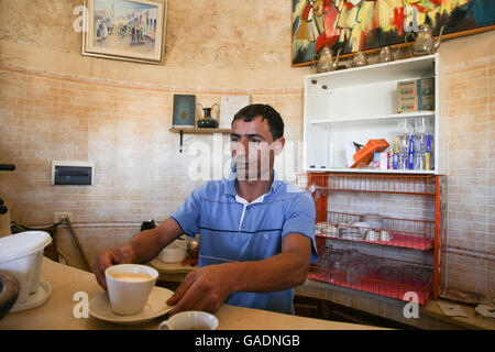 A man making coffee at Dar Ayed in Tamezret, Tunisia. Dar Ayed is a tourist point that offers a panoramic view of - Stock Photo