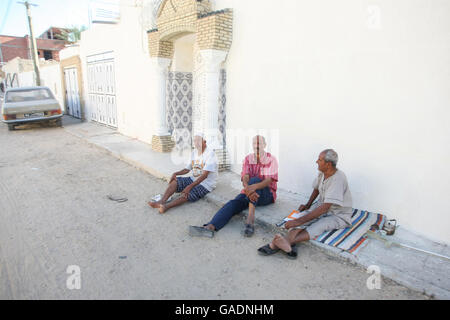 TOZEUR, TUNISIA - SEPTEMBER 16, 2012 : Three tunisian men sitting on the pavement in front of the house in Tozeur, - Stock Photo