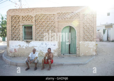 TOZEUR, TUNISIA - SEPTEMBER 16, 2012 : Two tunisian men sitting on the pavement in front of the house in Tozeur, - Stock Photo