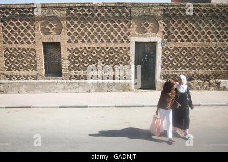 TOZEUR, TUNISIA - SEPTEMBER 16, 2012 : Two tunisian women crossing the street in Tozeur, Tunisia. - Stock Photo