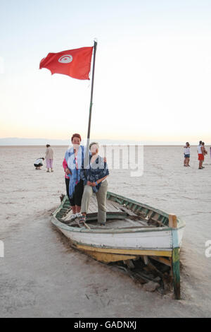 Tourists on an abandoned boat with a Tunisian flag at Chott El Jerid, Tunisia. - Stock Photo