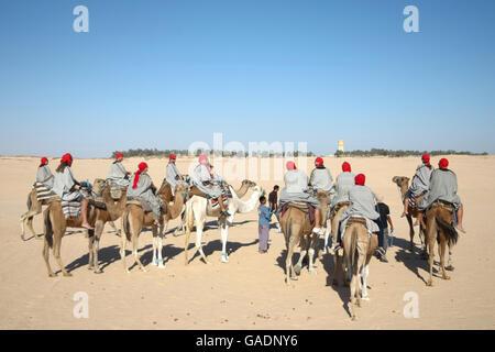 Bedouins leading tourists on camels at short tourist tour around the beginning of Sahara desert in Douz, Tunisia. - Stock Photo