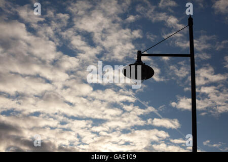 A solitary lamp post silhouetted against a cloudy sky - Stock Photo