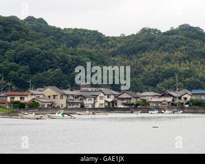 Small fishing boats and pleasure craft in front of traditional Japanese houses, - Stock Photo