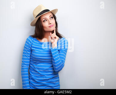 Grimacing young lady in summer hat thinking and looking up on blue background - Stock Photo