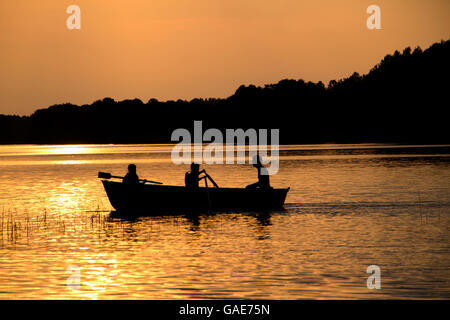 rowing wooden boat on lake in late evening with two girls and father people silhouettes - Stock Photo