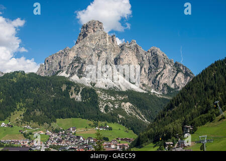 The touristic village of Corvara (1568 mt.) in Val Badia under the huge Sasshonger (2665 mt). - Stock Photo