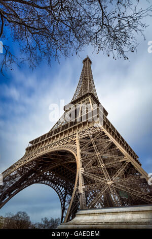 Low angle view Eiffel Tower and passing clouds, Paris, France - Stock Photo