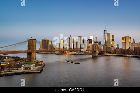 Aerial view of the Brooklyn Bridge at sunrise with Manhattan Financial District skyscrapers and the East River. - Stock Photo