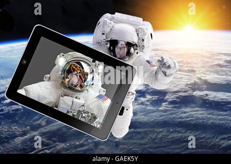 Astronaut in outer space with tablet - Elements of this image furnished by NASA - Stock Photo