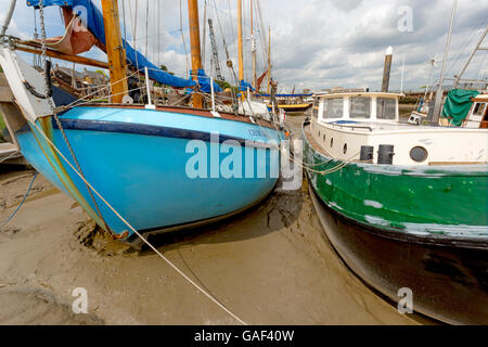 Marooned sailing yacht and barge raised up on sand and silty mud on River Chelmer, Maldon, Essex, England, United Kingdom.