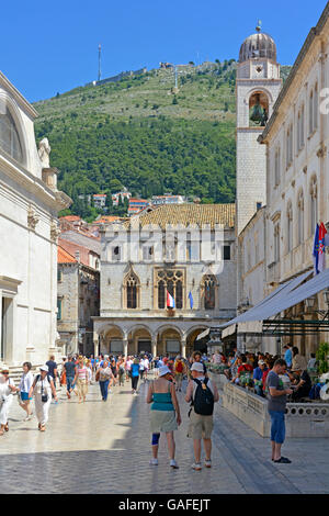 Street scene of tourists in the Old Town in Dubrovnik Croatia with the Sponza Palace and Bell Tower in Luza Square blue sky sunny day