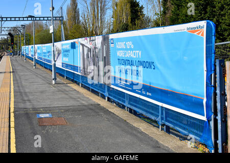 Network Rail adverts construction site hoarding adding Crossrail platform & track to the existing Shenfield UK station - Stock Photo