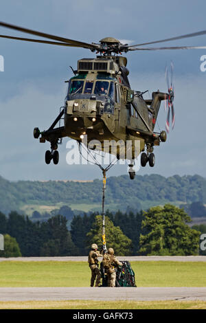 A Royal Navy Westland Sea King Mk 4 is hooked up to an underslung load at the RNAS Yeovilton International AirDay - Stock Photo