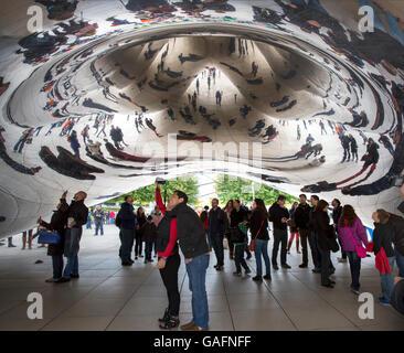 Tourists taking photos under the Cloud Gate sculpture in Millennium Park, Chicago, Illinois. - Stock Photo