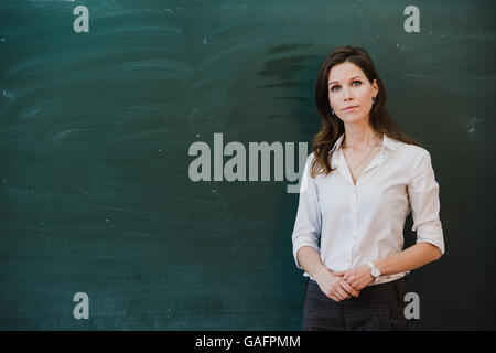 Closeup of young female teacher against chalkboard in class - Stock Photo