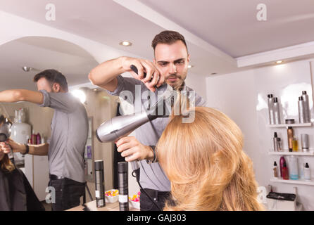 man hairstylist blow drying comb roller woman hair, side view - Stock Photo