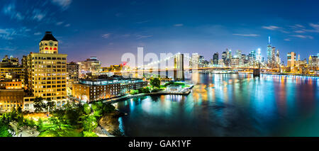 New York City panorama by night. Brooklyn Bridge spans East River linking Manhattan and Brooklyn boroughs - Stock Photo