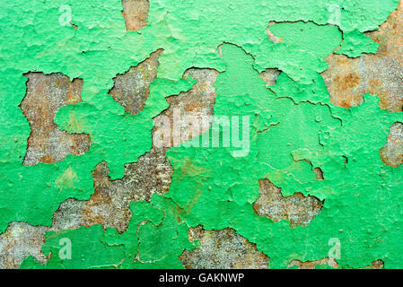 Green flaking paint falling off of a rusty metal surface with split and cracking paints holes. - Stock Photo