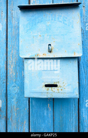 Blue retro style metal post box on a wooden blue domestic fence - Stock Photo