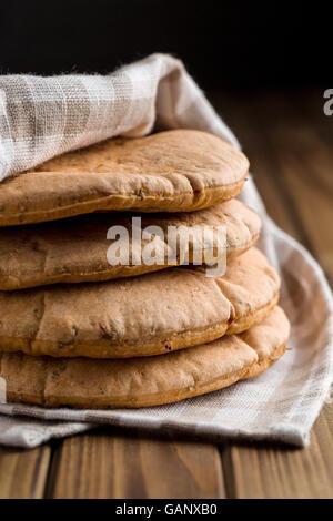 Tasty pita bread on old wooden table. - Stock Photo