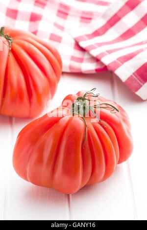 Coeur De Boeuf. Beefsteak tomatoes on white table. - Stock Photo