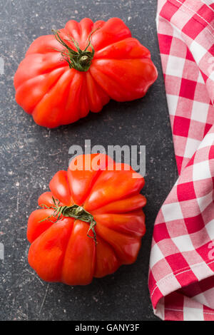 Coeur De Boeuf. Beefsteak tomatoes on old kitchen table. - Stock Photo