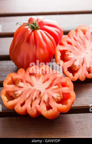 Coeur De Boeuf. Beefsteak tomatoes on wooden table. - Stock Photo