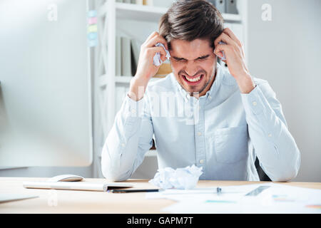 Aggressive angry young businessman holding crumpled paper sitting at his workplace - Stock Photo