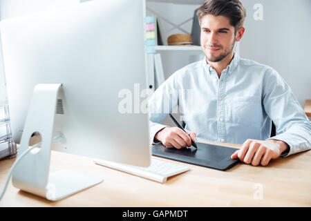 Happy young man designer working using computer and graphic tablet at workplace - Stock Photo