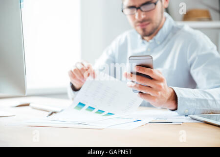 Cropped image of a happy young businessman using mobile phone while working in the office - Stock Photo