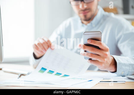 Cropped image of a pensive young businessman using mobile phone while working in the office - Stock Photo