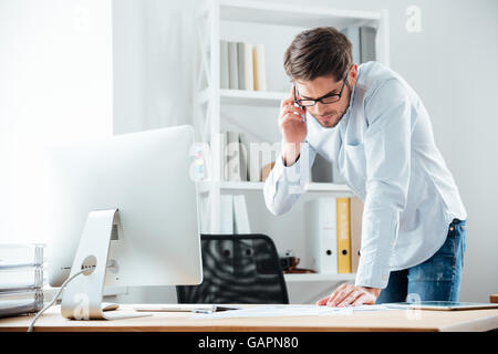 Young handsoome business man standing at desk working on documents with mobile phoone in office - Stock Photo