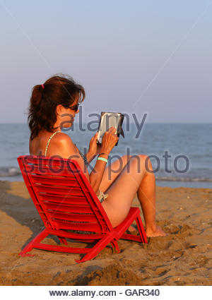 Woman reads the ebook on the beach by the sea in summer stock pretty woman on red chair reads the ebook on the beach by the sea in summer fandeluxe Ebook collections