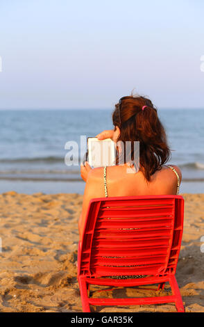 Woman reads the ebook on the beach by the sea in summer stock pretty woman reads the ebook on the beach by the sea in summer stock photo fandeluxe Ebook collections