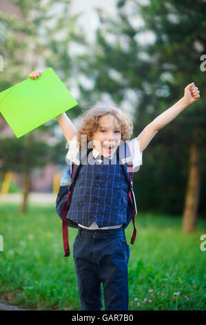 Little schoolboy rejoices. The boy raised up both hands. The student is smartly dressed. He looks at the camera - Stock Photo