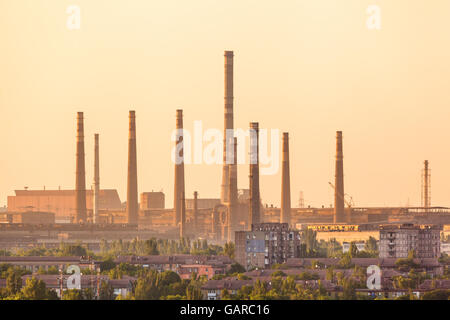 City buildings on the background of steel factory with smokestacks at colorful sunset. metallurgical plant. steelworks, iron wor