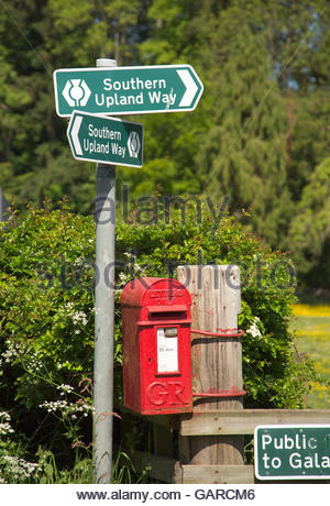 A Royal Mail post box and sign post for the Southern Upland Way - a long distance walking route at Fairnilee or - Stock Photo