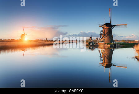 Beautiful traditional dutch windmills near the water channels with reflection in water at colorful sunrise in famous - Stock Photo