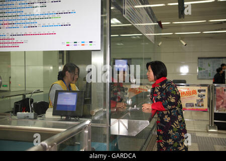 Chinese woman is a buying a ticket for the subway at a ticket booth in the Chedaogou Station.  Beijing, China. Stock Photo