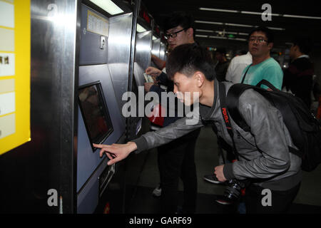 A Chinese man is using a machine to buy a ticket for the subway at the Zhongshan Subway Station. Shanghai, China. 30.04.2016. Stock Photo