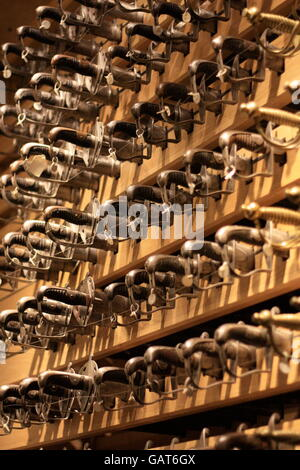 Swords in a rack at the Tower of London armoury - Stock Photo