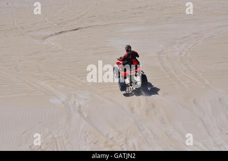 Lancelin,WA,Australia-September 28,2015:Lancelin Sand Dunes with person racing a red quad bike over the sand in - Stock Photo